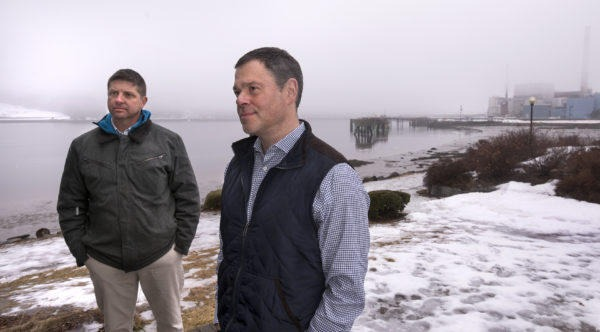 BUCKSPORT, MAINE — 02/20/2018 — Robert Piasio, CEO Of Whole Oceans, Right, And Ben Willauer, Director Of Corporate Development, Stand On The Bucksport Waterfront With The Former Verso Paper Mill In The Background. Whole Oceans Plans To Build A $250 Million Land-based Salmon Farm An The Northern Portion Of The Mill Site, The Second Such Farm Announced In Maine This Year. Gabor Degre | BDN